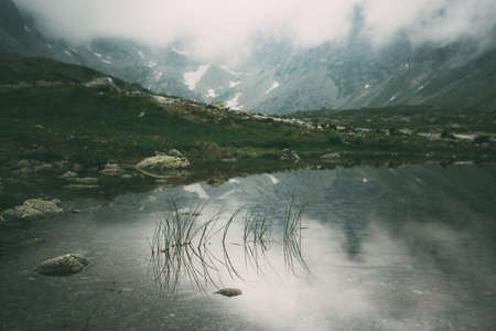Mountain lake Hincovo pleso in High Tatras. Slovakia. Natural misty landscape.
