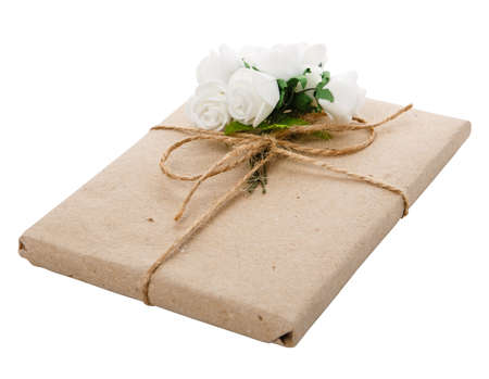Gift for special occasion wrapped in kraft paper with burlap ribbon and floral decoration. Isolated on white background and clipping path cutout.