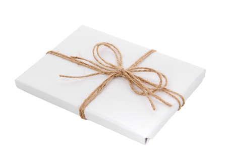 Gift wrapped in white paper with a bow made of burlap thread on a white background. 스톡 콘텐츠