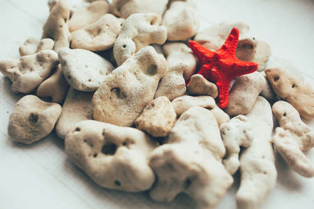 Natural pebbles with red starfish on a white background. Close, selective focus. 스톡 콘텐츠 - 151620572