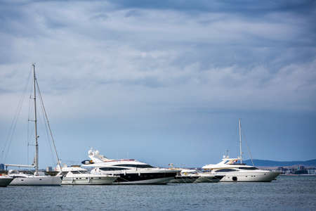 Several luxury white boats on water with reflections standing on pear in sea port 스톡 콘텐츠 - 151620734
