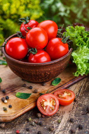 Cooking background. Fresh vegetables and peppers on wooden background. Ripe tomatoes and herbs. Food photo.
