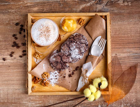 Cinnamon coffee, orange jam and homemade chocolate chip cookies. Dessert lies on kraft paper and coffee in paper cup. On the side are eco dishes and decorative branches of cotton. Top view. Flatlay.