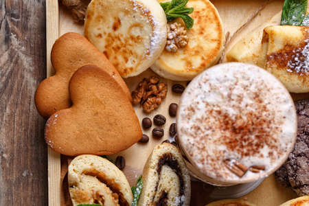 Coffee and cookies on rustic wooden background. Cinnamon coffee and cookies, cheesecakes and strudel are decorated with powdered sugar, nuts and mint. Top view, close up, selective focus. Promotional shooting. 스톡 콘텐츠