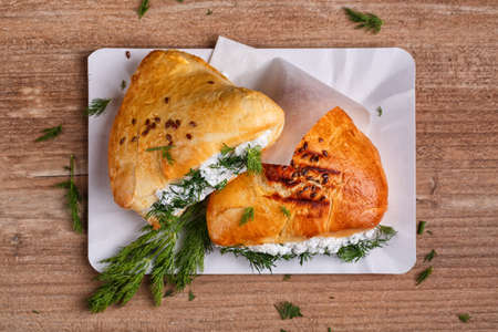 Fried pies with cottage cheese filling. Patties with cottage cheese and dill. Cheap recipe for homemade fried pies on a wooden background in rustic style. Easy meal idea. Close-up, top view. 스톡 콘텐츠 - 151620744