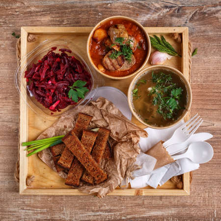 Ukrainian traditional borscht and vegetable broth in paper cups, beet salad in a glass bowl, bread crumbs and green onions on a rustic wooden tray. Ukrainian dishes. Ukrainian menu.