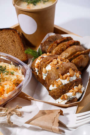 Disposable tableware, soup in a paper cup, bread, salad and baked potatoes with cottage cheese and nuts on a wooden tray on a white background. Blurred background, close up.