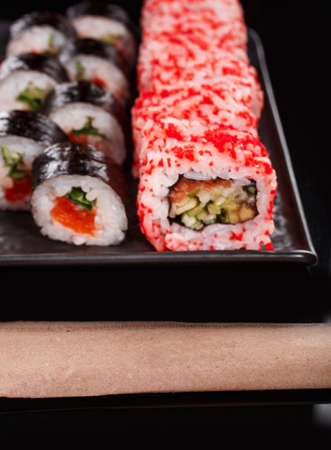 Sushi set of Uramaki and Maki with red caviar, salmon and cucumber. Served on a black plate. Japanese food. 스톡 콘텐츠