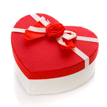 Red and white gift box in the form of a heart with a flower in the middle. Isolated on white background. Surprise for the holidays.