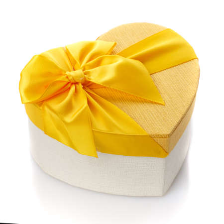 Yellow and white gift box in the form of a heart with a large yellow bow. Isolated on white background. Surprise for the holidays.