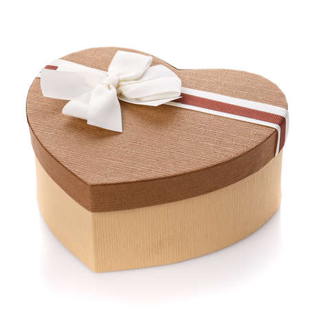 A brown gift box in the form of a heart with a white bow. Isolated on white background. Surprise for the holidays. 스톡 콘텐츠