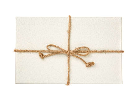 White gift box with burlap ribbon on a white background. Top view. 스톡 콘텐츠