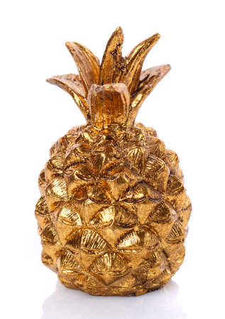Ceramic decorative statuette of golden pineapple on white background.