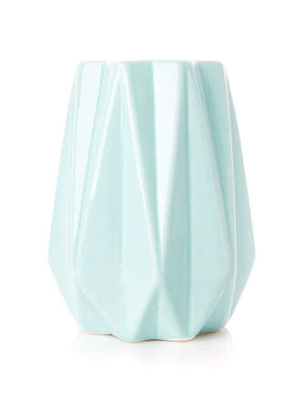 Decorative ribbed vase of turquoise color on a white background. Modern home decor.