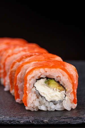 Beautiful sushi roll topped with salmon stuffed with cream cheese on a black stone board. Sushi menus.