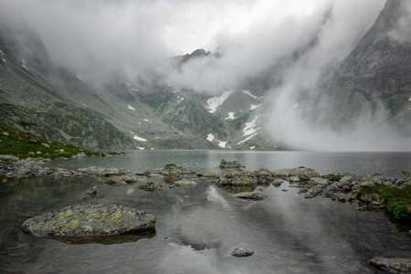 Hincovo pleso in the fog between the mountains. High Tatras of Slovakia. Mountain lake and mountains are covered with fog. 스톡 콘텐츠
