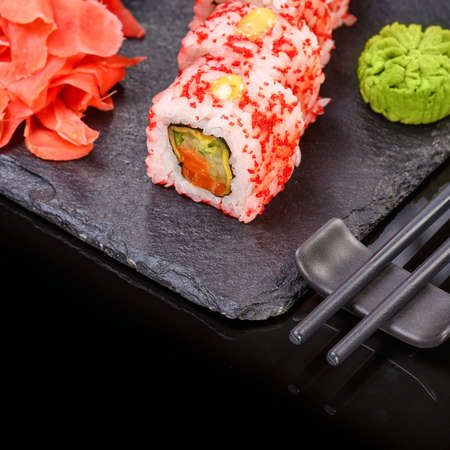 Sushi roll with seafood and soy sauce, wasabi and ginger. Sushi roll with caviar on a black board. 스톡 콘텐츠