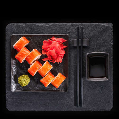 Japanese restaurant, sushi roll on black slate. Set with chopsticks, ginger and wasabi on a dark background. Top view.