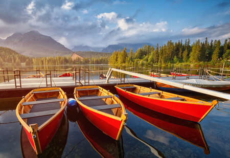 The colorful boats on Strbske lake in Slovakia. High Tatras mountains national park and beautiful mountain lake in the High Tatras. 스톡 콘텐츠