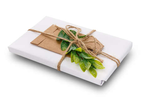 Decorated gift with green branch, burlap ribbon, greeting tag and wrapped in white paper. Isolated on white background