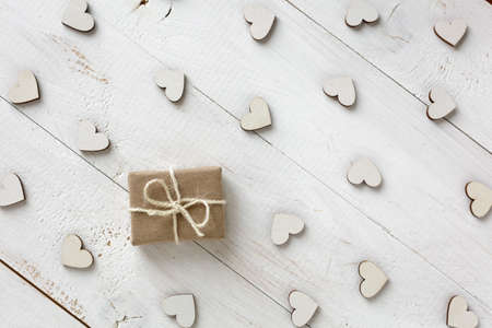Handmade gift in kraft paper on a white background. Wooden decorative hearts around gift. Valentine or other holiday.