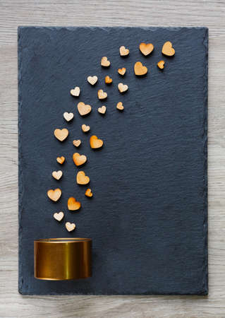 Love concept. Little wooden hearts falling out of a small gold gift box on a dark background. Top view with copy space
