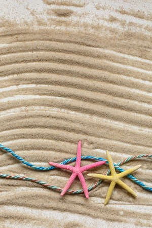 Starfish and colored ropes on a background of wavy sand. Souvenirs for travel, travel, leisure. Marine cruise theme. Top view with place for text. Sea, sand, beach.
