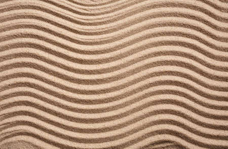 Textured wavy sand. The waves on the sand in the form of a zigzag. Sand dunes and beaches. Top view. Place for text.