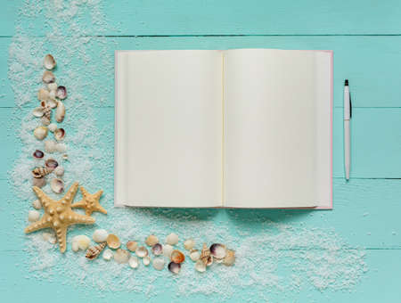 Summer template. Travel Planning. Notepad and pen, small seashells, starfish and sea salt on turquoise wooden background. Place for text on blank white notepad pages. Travel concept, flat lay, top view.