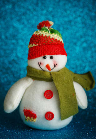 Snowman toy on blue background. New Year decoration
