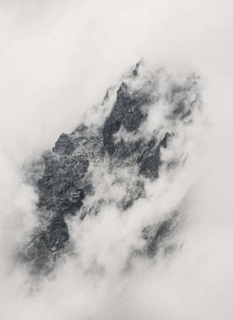 Mountain peak in clouds in Slovakia close up. High Tatras Mountains. White and black. Standard-Bild