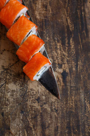 Sushi rolls with vegetables, cheese and salmon are laid out on a knife blade. On a rustic blackboard.