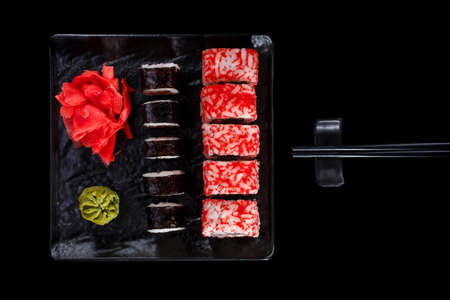 Japanese restaurant, sushi roll on black slate. Set with chopsticks, ginger and wasabi on a dark background. Stock fotó