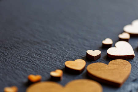 Little light wooden hearts on a dark background. Valentines Day. Love concept. Place for text. 스톡 콘텐츠
