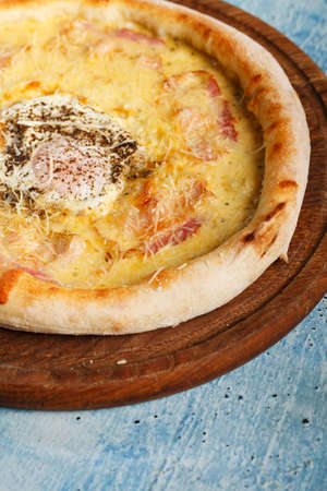 Breakfast pizza with egg on a blue wooden table with copy space. Banque d'images