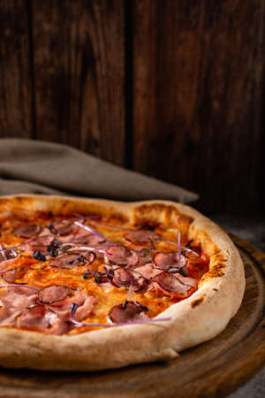Delicious pizza on a wooden background close up. Pizza with meat, cheese and basil. Selective focus.