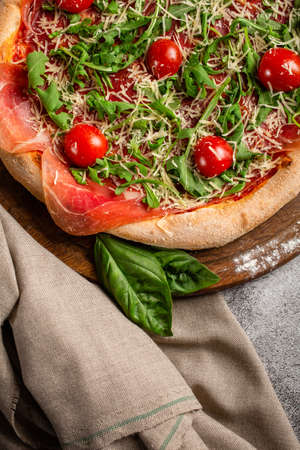 Pizza with arugula and cherry tomatoes on wooden board. Fresh homemade pizza. Banque d'images