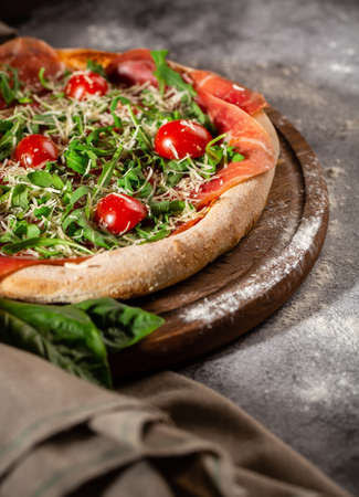 Pizza close up with arugula, prosciutto and cherry tomatoes on a wooden board. Photo for the menu.