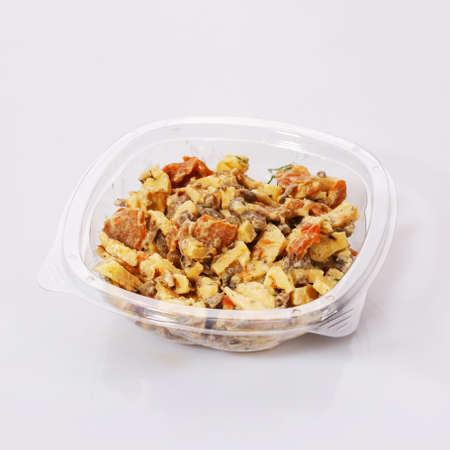 Salad of carrots, meat, cheese and sauce in a transparent plastic bowl on a white background.