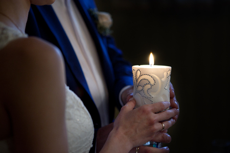 bride and groom holding a candle photo