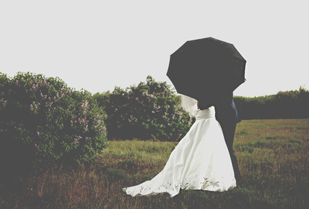 bride and groom under umbrella photo