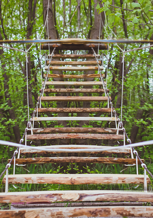 rope bridge: Wooden stairs in the green forest park with ropes