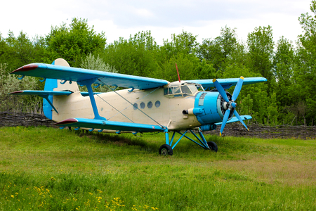 Old retro airplane on green grass field
