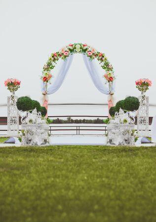 結婚式: 川での結婚式。コンポジションの中心に花で飾られたアーチ