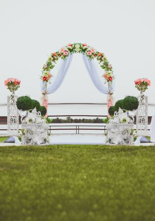 cérémonie de mariage: Wedding ceremony by the river. Arch decorated with flowers in the center of the composition