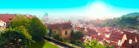 Panorama of Prague in Czech Republic with red roofs, blue sky and green grass. Sunny day