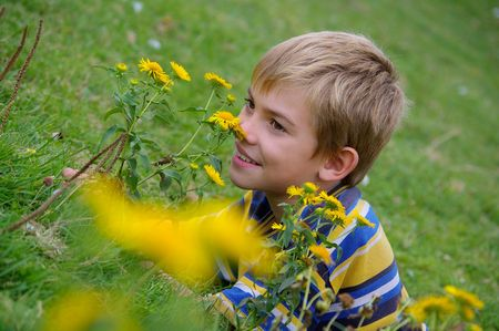 The boy portrait against background of grass and flowers