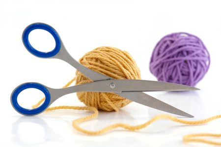 Two balls with yarn and scissors against the white background