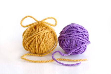 Two balls with yarn against the white background