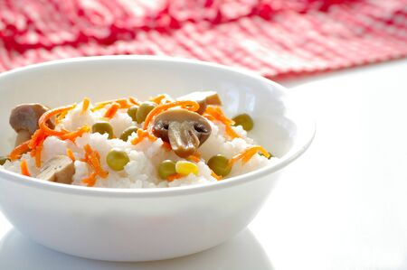 Plate with the rice and the vegetables on the kitchen table  Stock Photo